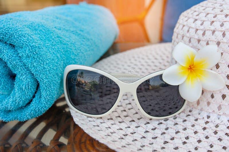 Solglasögon är på hatten och blomman på stranden royaltyfria bilder