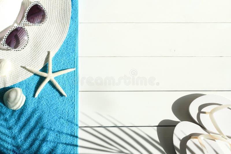 Solglasögon bläddrar misslyckanden, snäckskal, sommarsugrör och den blåa strandhandduken på vit träbakgrund arkivfoto