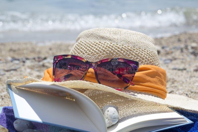 Solglasögon för sugrörhatt och en bok på stranden royaltyfri bild
