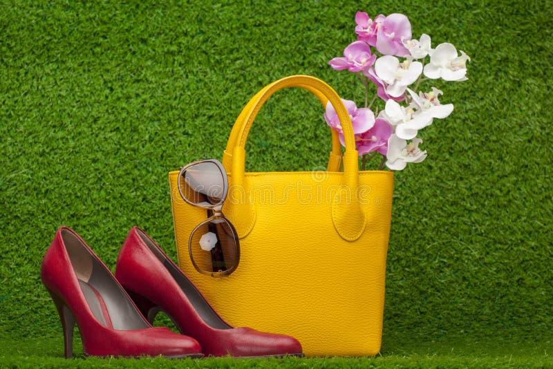 Solglasögon handväska; och röda skor royaltyfria foton