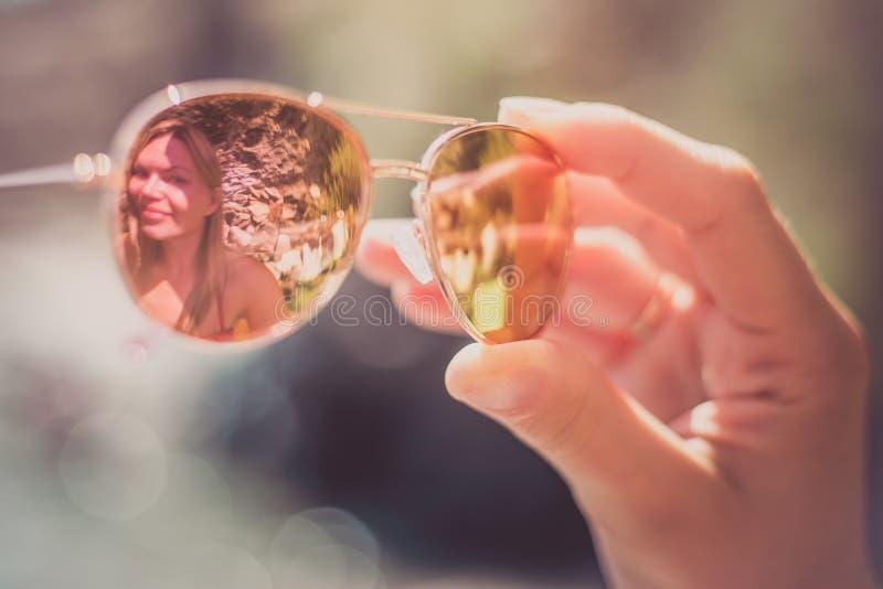 Solglasögon i kvinnlig hand på stranden med henne reflexion royaltyfri fotografi