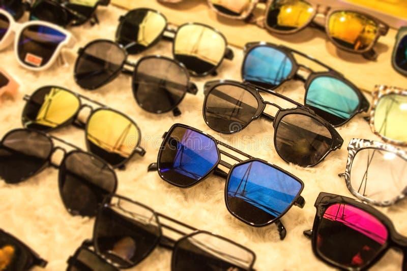 Solglasögon i många mörka UV skuggor för olika stilar Att shoppa för rabatter och försäljningar på monokelmarknaden shoppar Få di arkivfoton