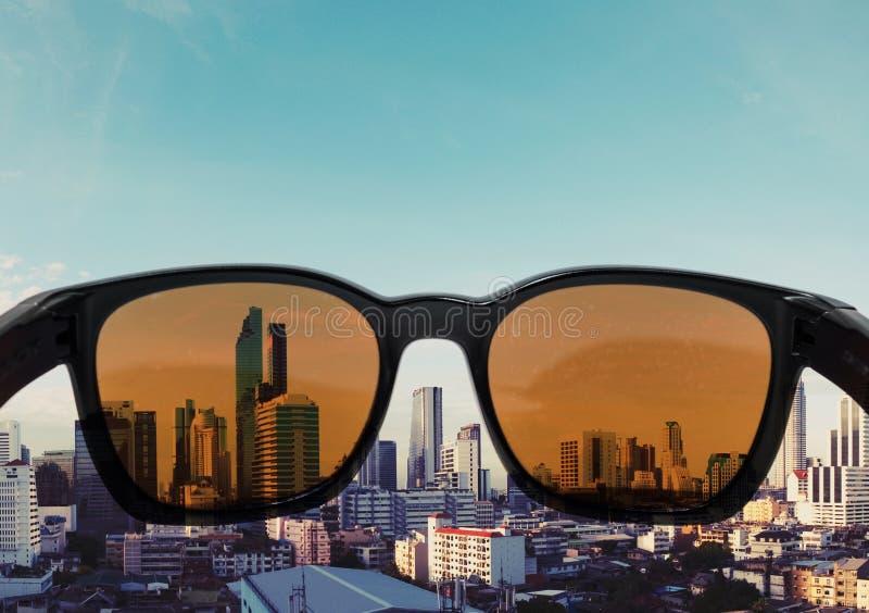 Solglasögon med ljus - brun lins som ser till stadssikten royaltyfri fotografi