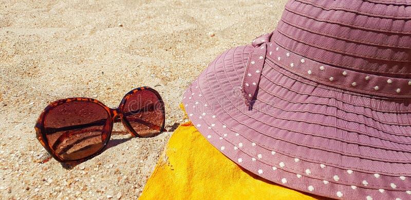Solglasögon och hatt på sand Tillbehör till semesterbussar royaltyfri bild