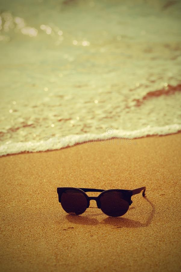Solglasögon och sandig kust med vågen i retro stil royaltyfria bilder