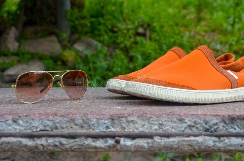 Solglasögon och skor royaltyfri bild