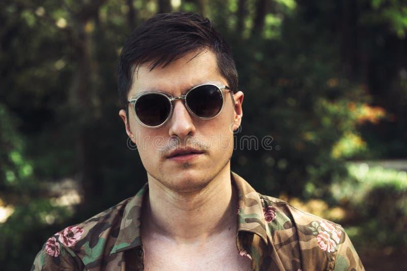 Solglasögon och t-skjorta för stilig man bärande på sommarsemester royaltyfri foto