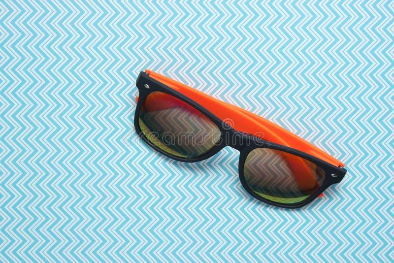 Solglasögon på en idérik blå bakgrund, minimalism, bästa sikt royaltyfri bild
