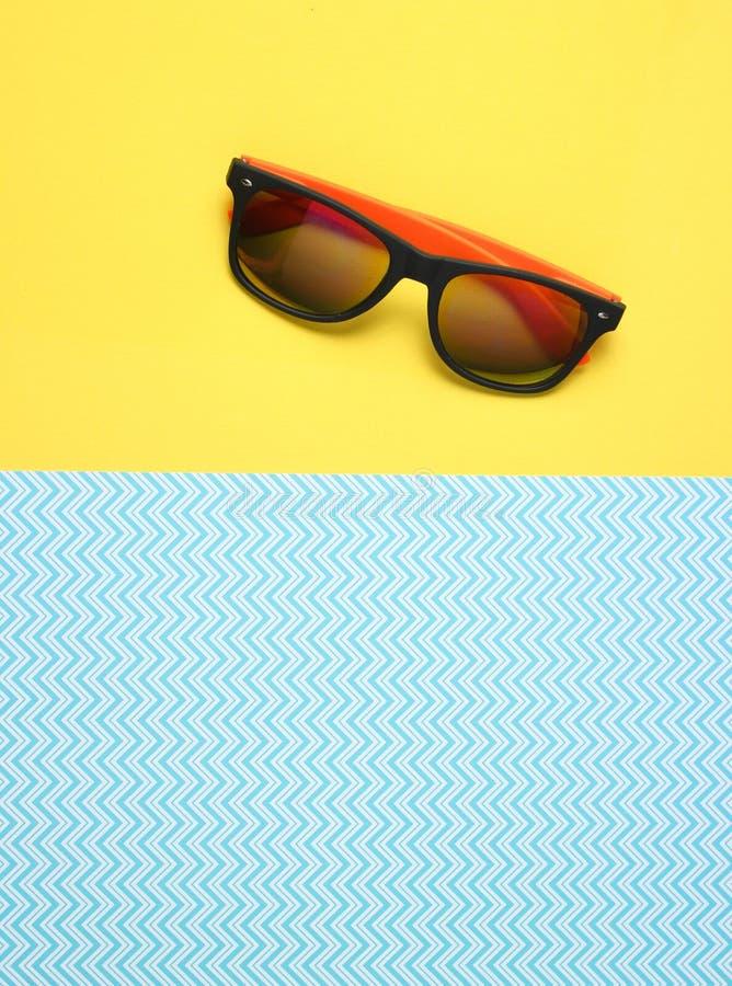 Solglasögon på en idérik blå gul bakgrund, sommartid, minimalism, bästa sikt royaltyfria bilder