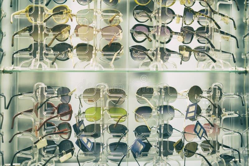 Solglasögon på exponeringsglashyllor i shoppar fönstret, en sommartillbehör royaltyfria bilder