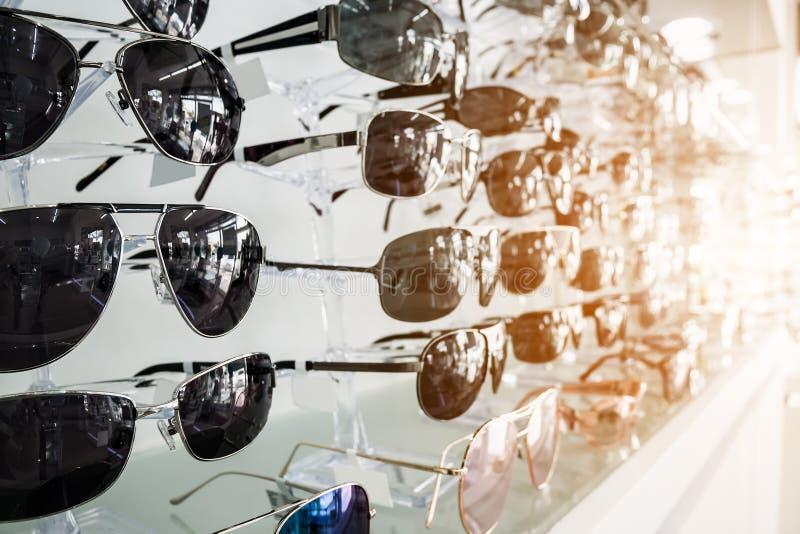 Solglasögon på hyllor i exponeringsglaslager arkivfoto