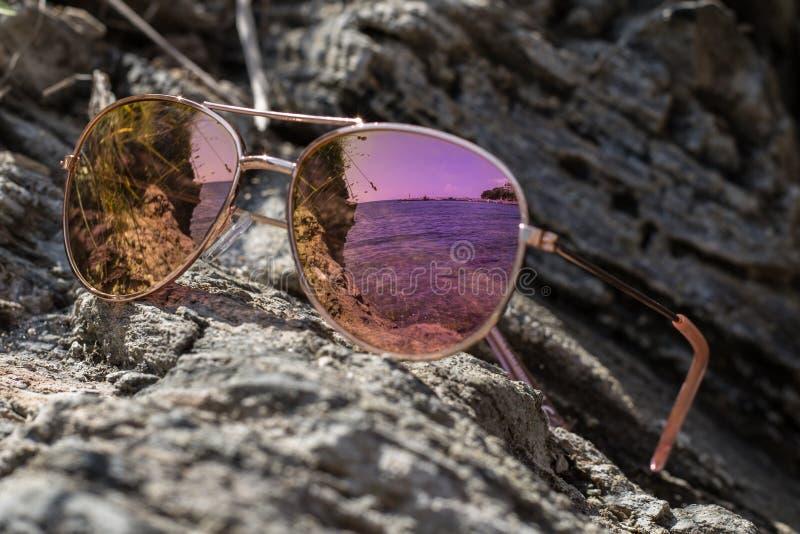 Solglasögon på stranden med havsreflexion arkivfoton