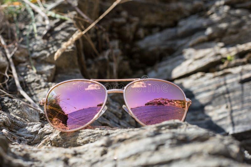 Solglasögon på stranden med havsreflexion royaltyfri foto