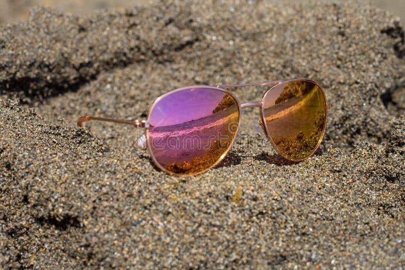 Solglasögon på stranden med havsreflexion royaltyfria bilder