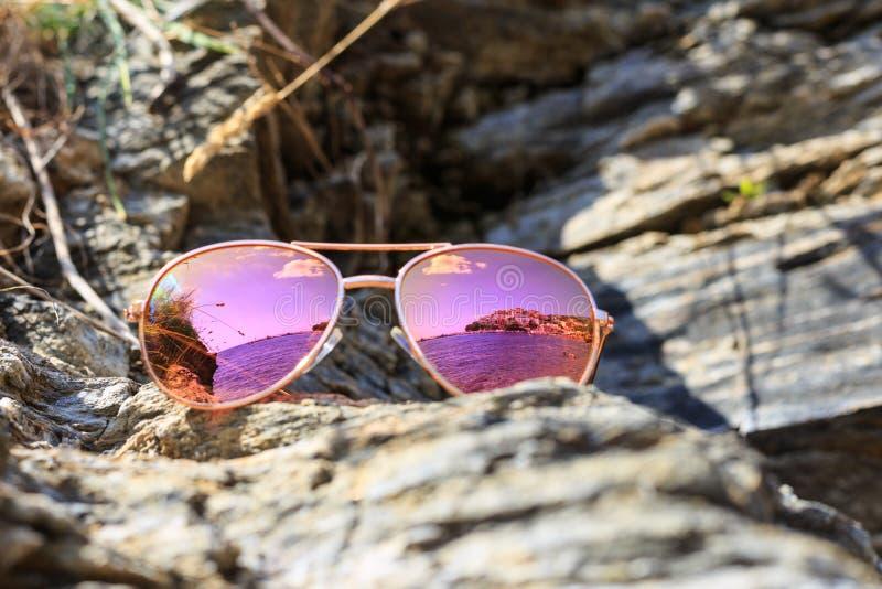 Solglasögon på stranden med havsreflexion arkivbilder