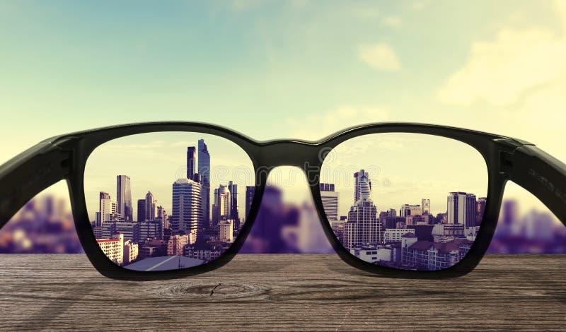 Solglasögon på träskrivbordet som fokuseras på linsstadssikt royaltyfri bild