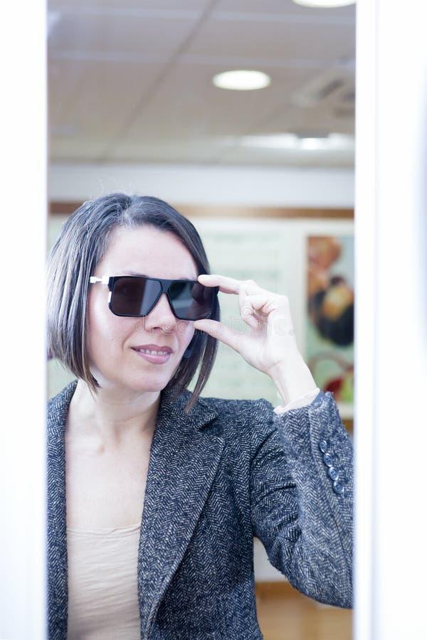 solglasögon som försöker kvinnan royaltyfri fotografi