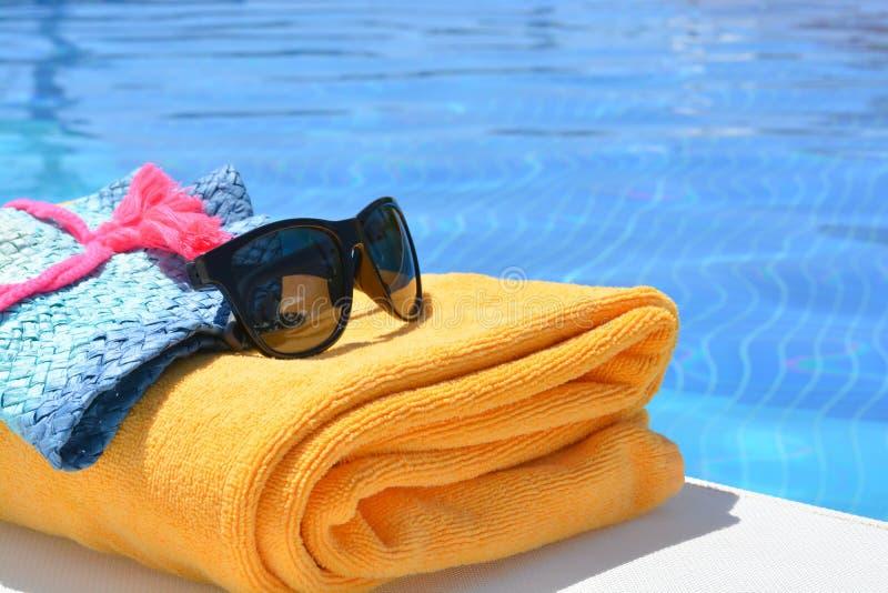 Solglasögonhandduk och en hatt nära en simbassäng på en sommardag royaltyfria bilder
