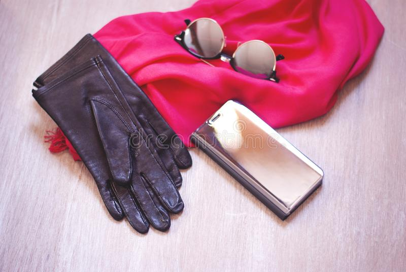 Solglas?gon f?r f?r spegeltelefonfall och spegel och rosa halsduk p? tr?tabellen royaltyfria foton