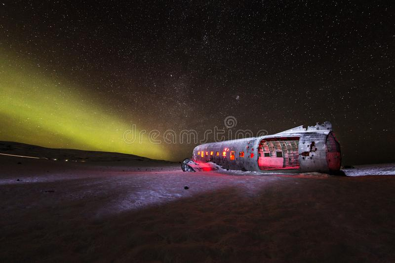 Solheimasandur plane wreck with active norhtern lights, Iceland. royalty free stock image