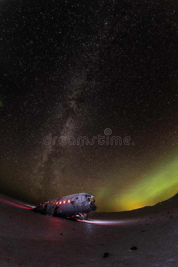 Solheimasandur plane wreck with active norhtern lights, Iceland. royalty free stock photos