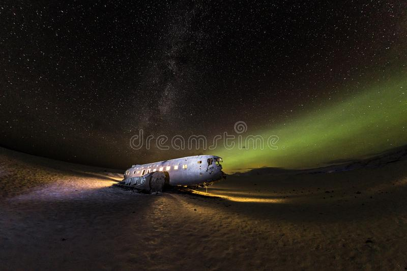 Solheimasandur plane wreck with active norhtern lights, Iceland. royalty free stock images