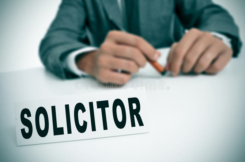 Solicitor. A man wearing a suit sitting in a desk with a desktop nameplate in front of him with the word solicitor royalty free stock photography