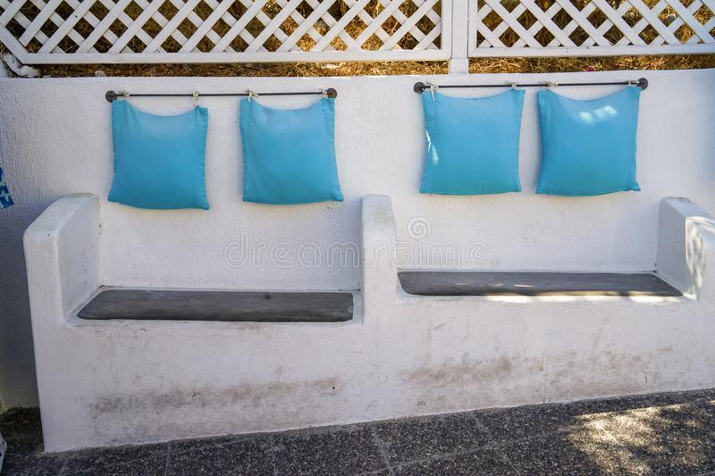 Solid built-in white concrete custom design bench seat chair with light blue pillow hanging by steel rod along island walkway. Santorini, Greece stock photos