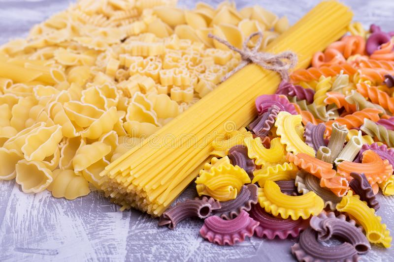 Solid and colored pasta close-up. Half of colored pasta, half plain. Funny pasta royalty free stock photography