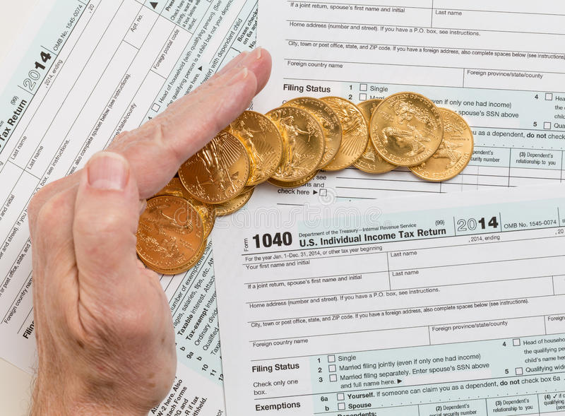 Solid gold coins on 2014 form 1040 stock photos