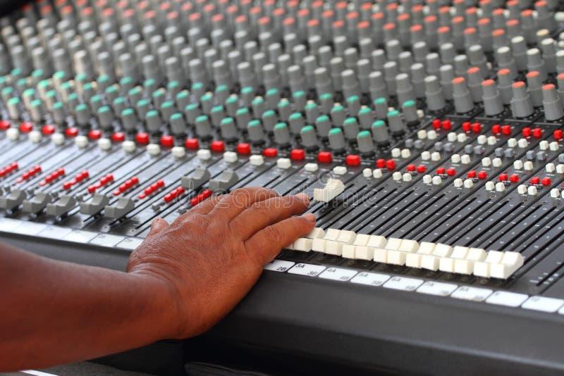 Solid hand för controler` som s justerar den ljudsignal blandaren royaltyfri fotografi
