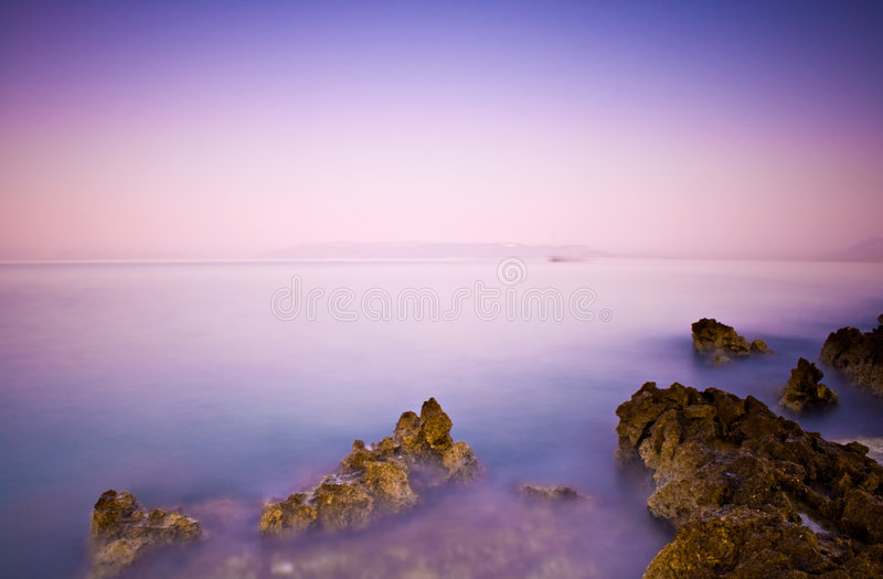 Solid rocks and a beautiful ocean at dusk stock photo