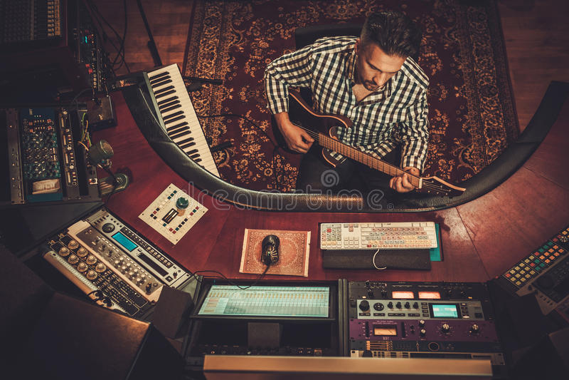 Solid tekniker med gitarren som arbetar i boutiqueinspelningstudio royaltyfri foto