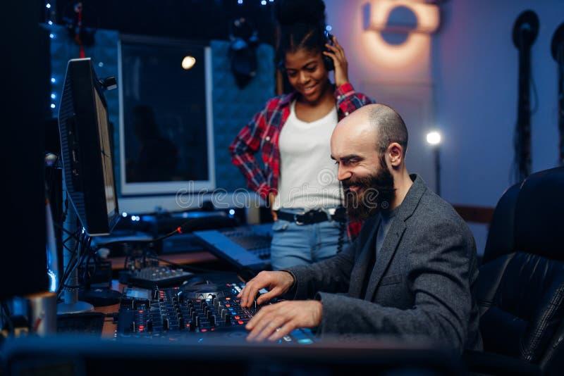 Solid tekniker och kvinnlig sångare, inspelningstudio royaltyfri bild