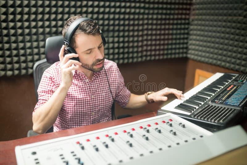Solid tekniker som arbetar i ljudtät inspelningstudio arkivfoto