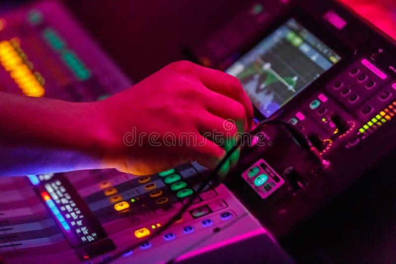 Solid tekniker som arbetar med konsolen för musik för solid equiplment- för konsert den ljudsignal blandande med bakbelysta knapp fotografering för bildbyråer