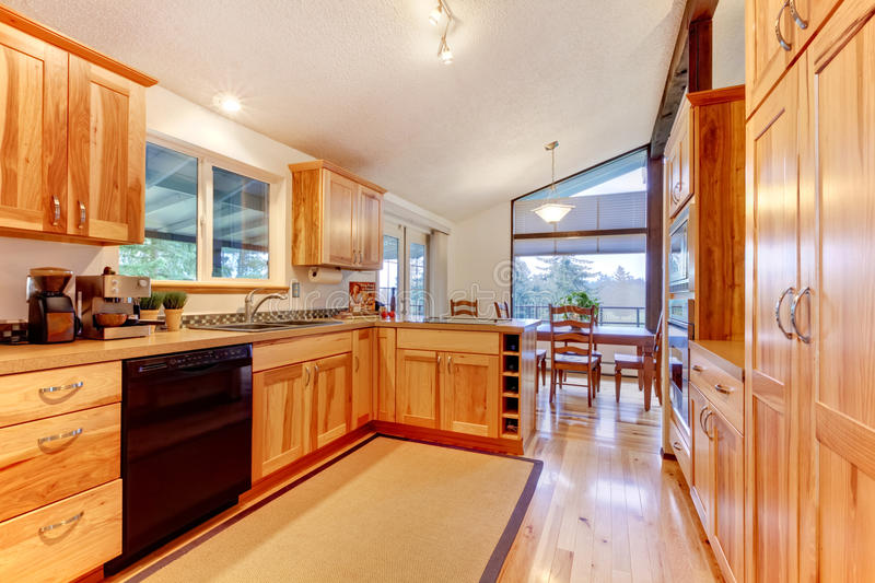 Solid wood birch kitchen custom made cabinets with hardwood floor. stock photography