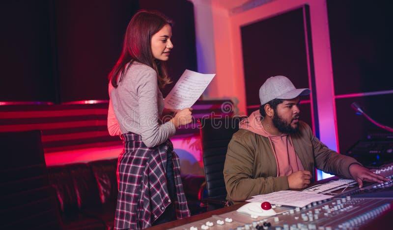 Solida teknikerer som arbetar i musikinspelningstudio arkivfoton