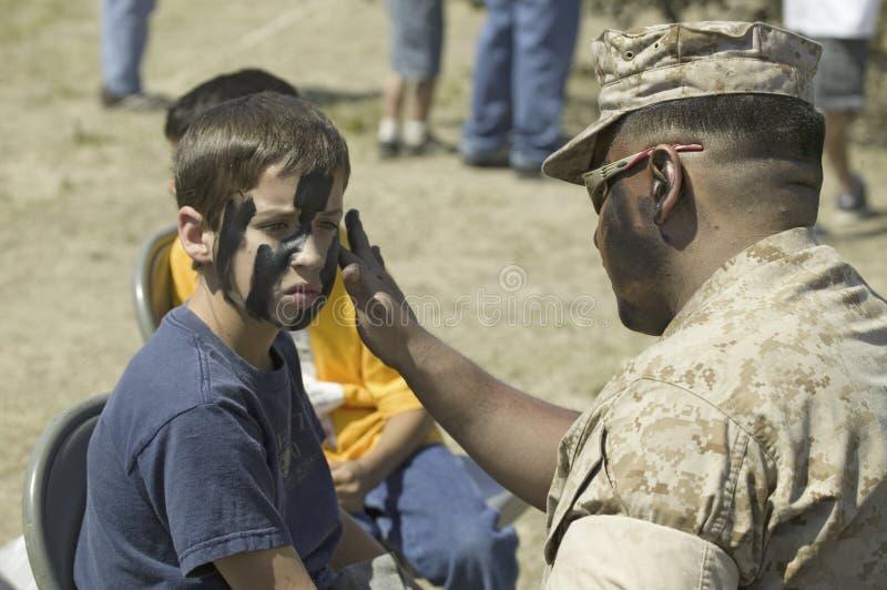 Solider dell'esercito che applica cammuffamento al giovane ragazzo immagine stock