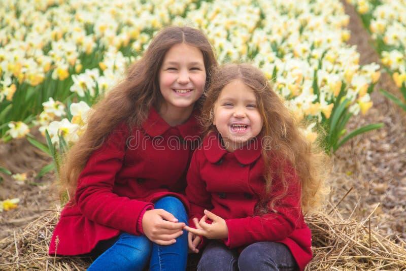 Solig dag för vår, första blommor och lyckliga barn fotografering för bildbyråer