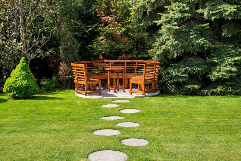 Solig dag i en vårträdgård med trätabellen och bänkar arkivbild