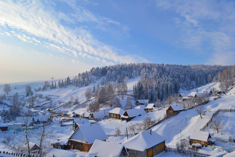Solig by för vinterdag och ryssi de Ural bergen, Ryssland Chelyabinsk region, Minyar, mycket insnöat byn royaltyfri bild