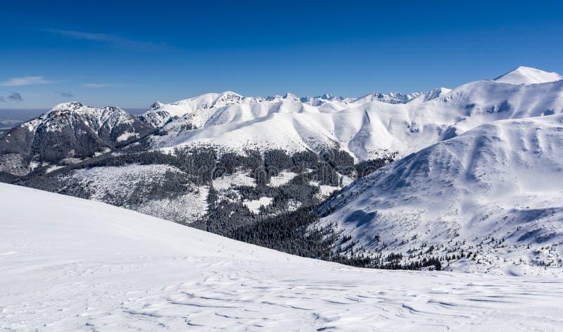 Solig frostig dag Blått gör klar himmel över bergkanter i snön royaltyfri bild