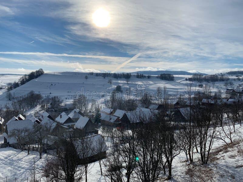 Solig knaprig vinterdag över by royaltyfria foton