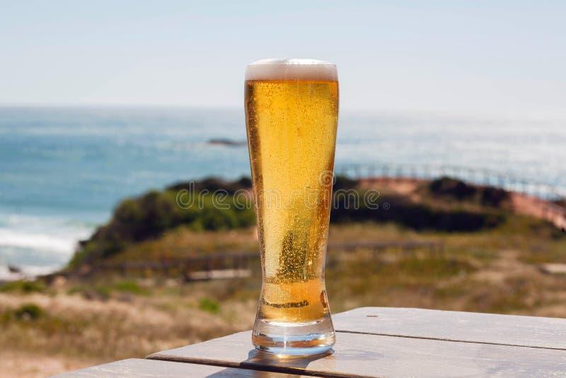 Solig kustlinje och ett ölexponeringsglas av en turist- havsikt med nytt öl på naturlig bakgrund h?rligt barn f?r kvinna f?r begr arkivfoton