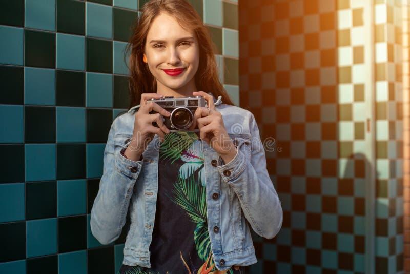 Solig modestående för livsstil av den unga stilfulla kvinnan som går på gatan, med kameran som ler för att tycka om helger fotografering för bildbyråer