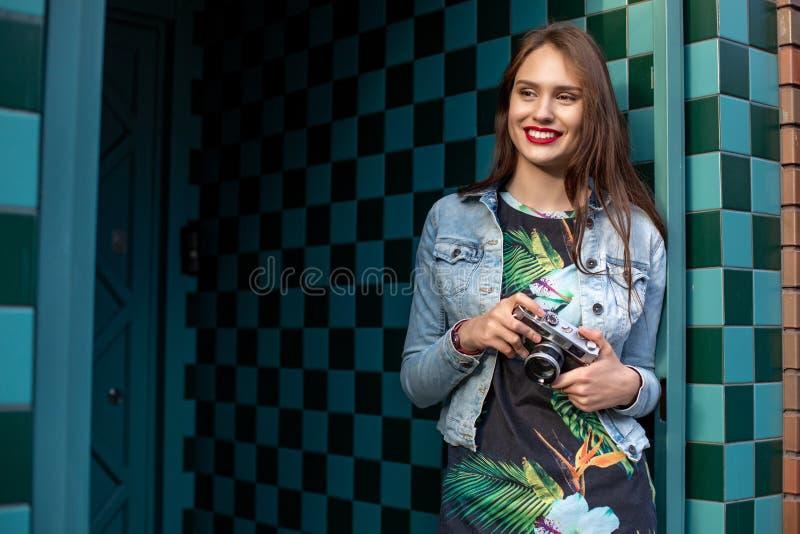 Solig modestående för livsstil av den unga stilfulla kvinnan som går på gatan, med kameran som ler för att tycka om helger arkivbild
