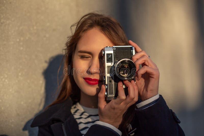Solig modestående för livsstil av den unga stilfulla kvinnan som går på gatan, med kameran som ler för att tycka om helger royaltyfria foton