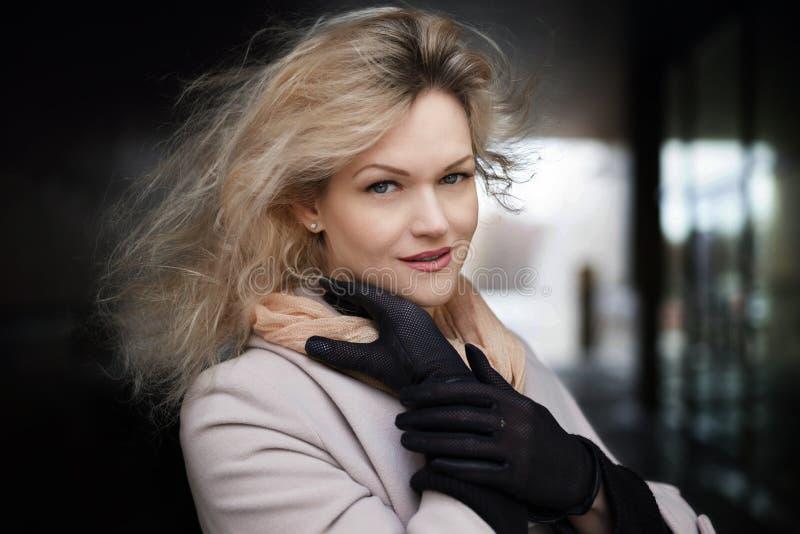Solig modestil f?r sommar St?ende av en ung stilfull kvinna utomhus, den ikl?dda moderiktiga dr?kten och svarta handskar royaltyfri foto