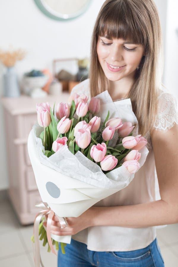 solig morgonfjäder Ung lycklig kvinna som rymmer en härlig grupp av rosa tulpan i hennes händer Gåva för en leendeflicka royaltyfria bilder